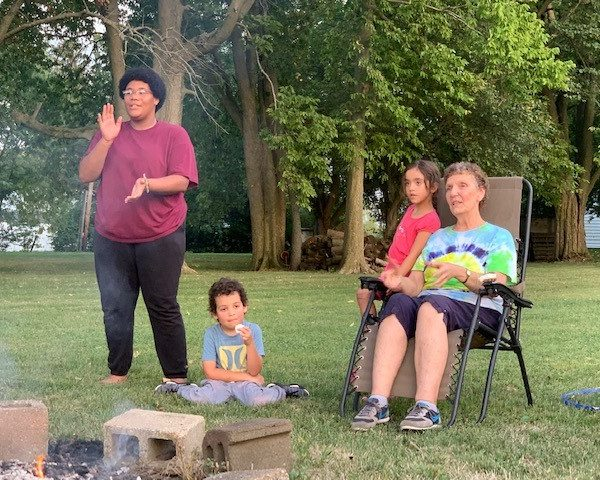 3 Youth and an adult at a campfire