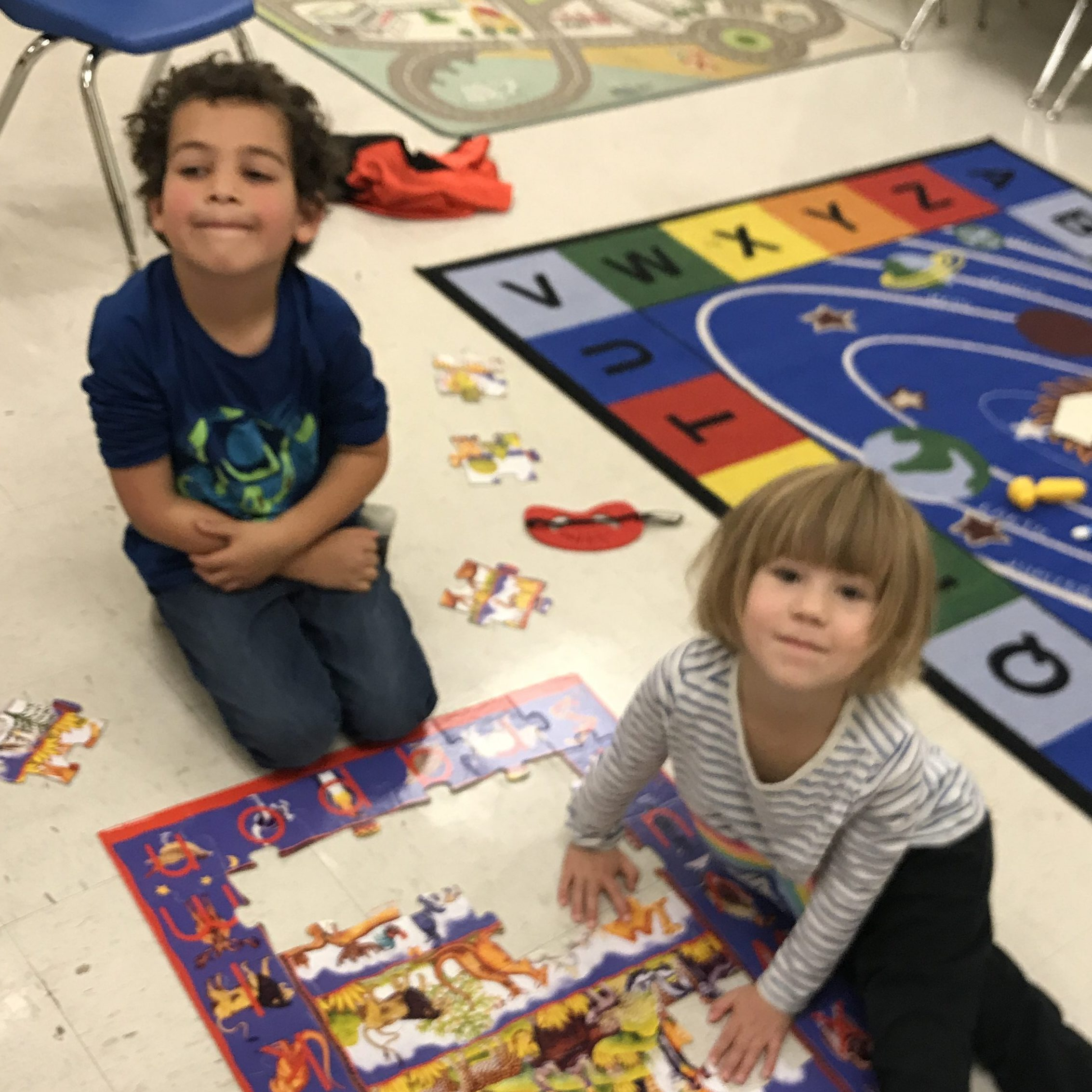 2 preschoolers playing on the floor of the nursery